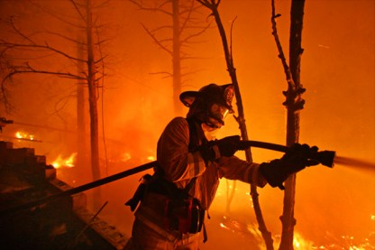 A Firefighter works to keep the fire away from homes along Circle View Drive as wildfires burn in Running Springs near Lake Arrowhead early (midnight)Tuesday morning October 23, 2007.