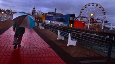 With the ferris wheel in the backround, a man with an umbrella braces himself against the rain as he makes his way along the Santa Monica Pier, Monday night in Santa Monica.