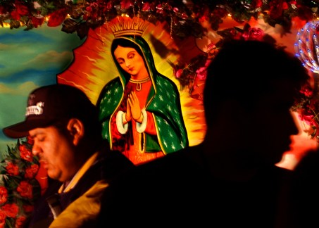 People turn into a colorful graphic as they blur past a Lady of Guadalupe backdrop along Olvera Steet during a celebration of El Dia de La Virgen De Guadalupe, Wednesday evening in downtown Los Angeles.It is a feast day and the start of the christmas season for the hispanic church, commemorates the appearance of the virgin.