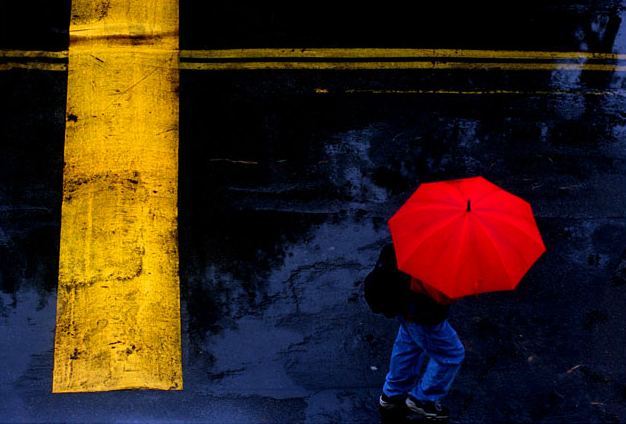 ME.Rain Art.Red.RH--012500--Toting a bright red umbrella, a student becomes part of a colorful graphic as he makes his way past a speeedbump while crossing campus in the rain at Saddleback College, Tuesday morning in Mission Viejo. Photo/Art by:Richard Hartog