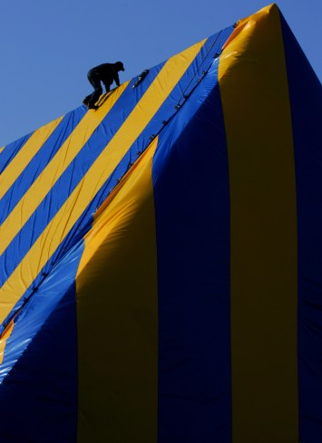 A worker becomes part of a graphic design as he is silhouetted atop a blue and yellow tarp while he prepares the building for fumigation on the roof at the Mount Olive Lutheran Church along Ocean Park Blvd. (and 14th) Friday in Santa Monica July 28, 2006.