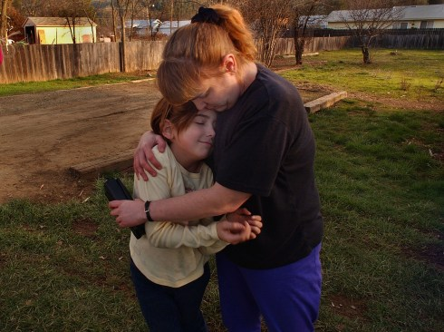 With not much time between her two jobs, Kelly Young and her daughter, Chantel, 10, share a tender moment outside their home in Hayfork, Ca. before Young must go to her second job, a graveyard shift taking care of an elderly client for $25 a night. Hayfork is one of California's poorest counties.