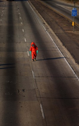 With an empty freeway behind him, a lone haz-mat worker makes his way towards a truck and its spill on the closed 710 freeway in South Gate, Ca.