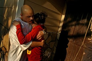 Brother Jose Arturo Saldana, left, comforts his sister Stacy Saldana on the front porch as they mourn the death of their father Arturo Saldana, 62, at his home in Norwalk, Tuesday, April 01. Saldana was one of two men slain in an East L.A. used car lot on Monday afternoon.