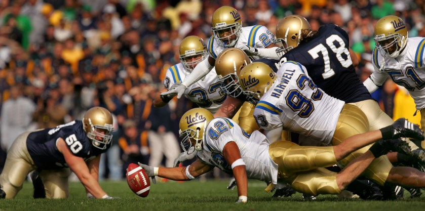 Notre Dame's Dan Santucci (#50), left, can only watch as UCLA linebacker Aaron Whittington stretches to recover a Fighting Irish fumble during first quarter at Notre Dame Stadium Saturday in South Bend, Indiana October 21, 2006.