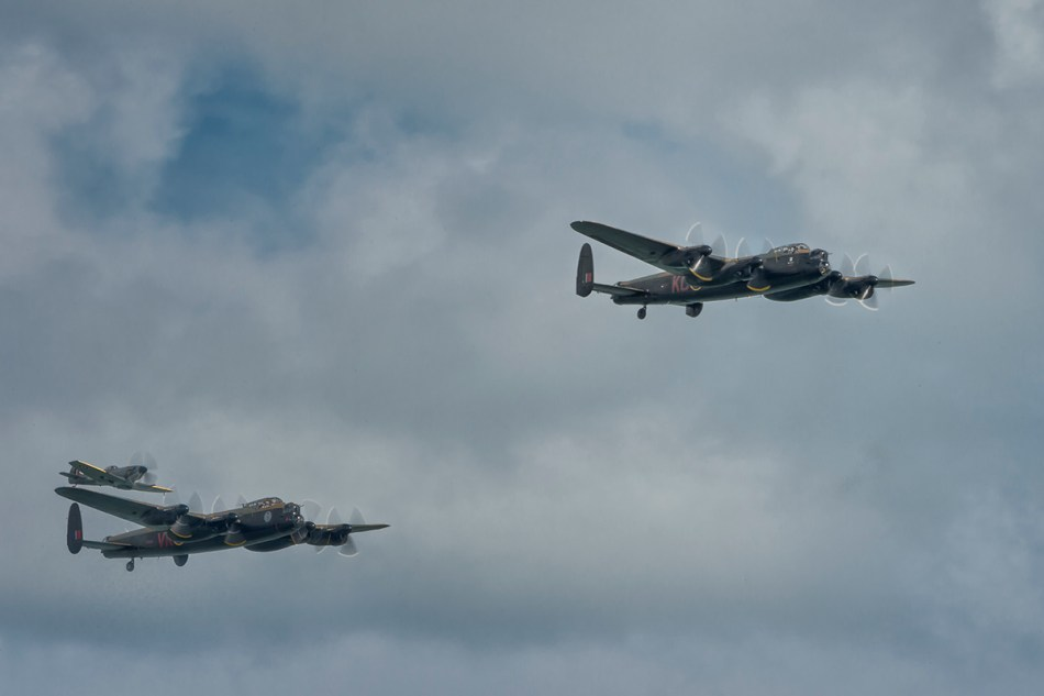 color photograph of two Avro Lancaster and a Supermarine Spitfire flying in formation