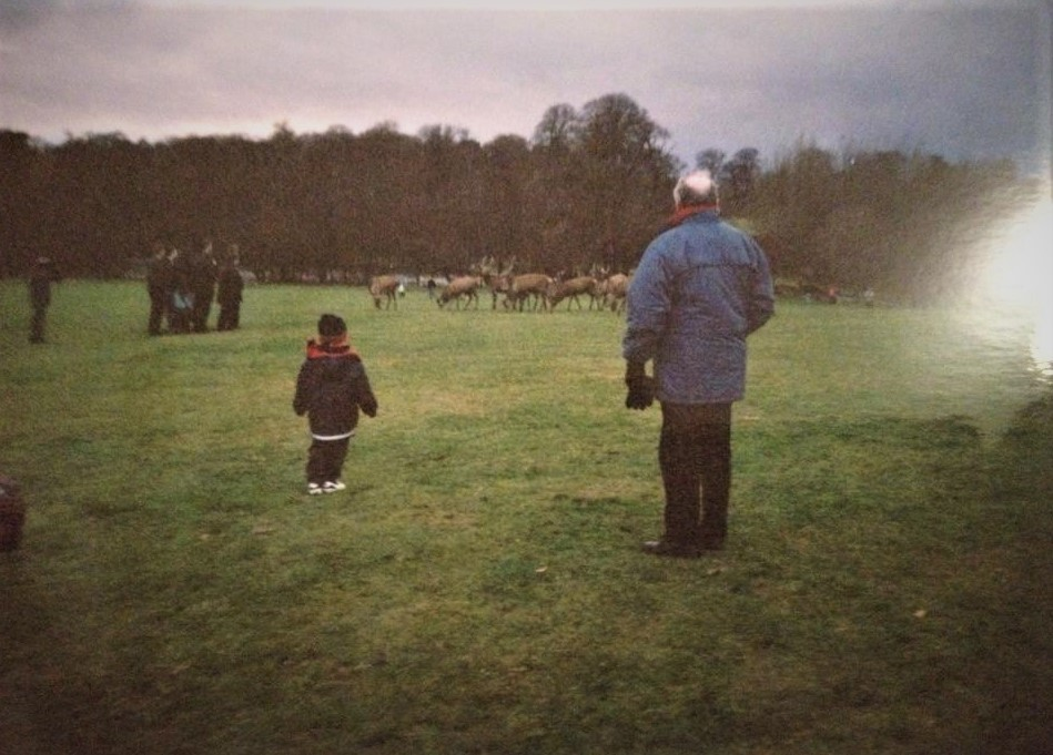 Richard and his grandad standing in a field looking at deer