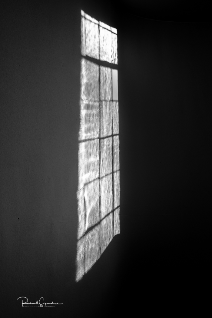shadows of a window playing on the opposite wall in a corridor