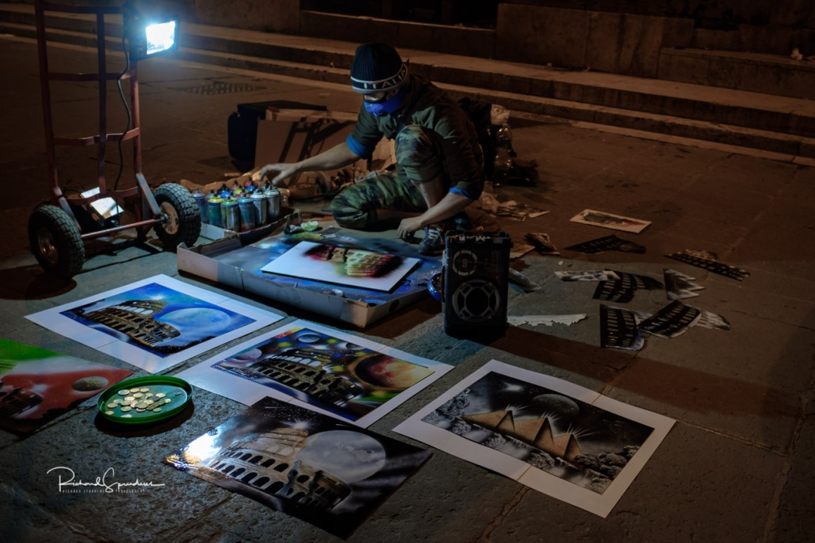 the image shows a street artist using spray cans paint to produce fantasy works of art he is work under his own protable flood light