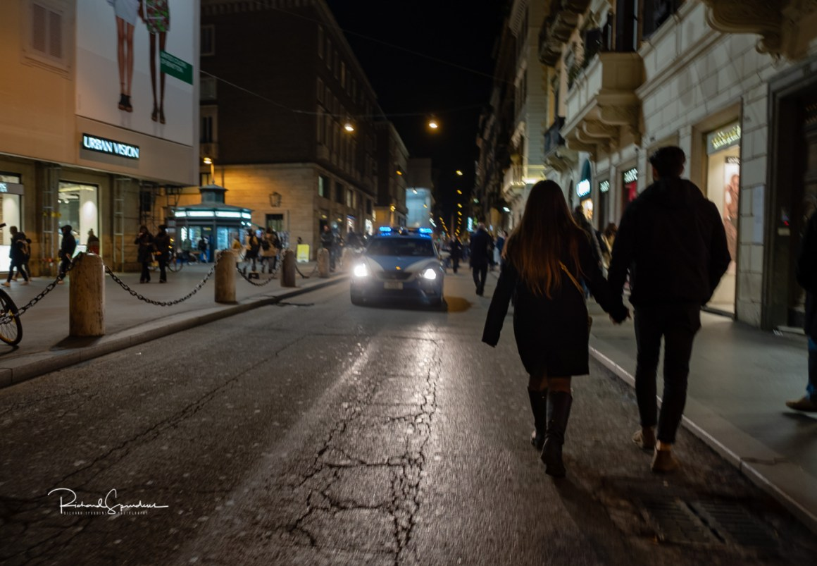 image from one of the main shopping streets showing a couple walking hand in hand against the on coming cars (februay images)