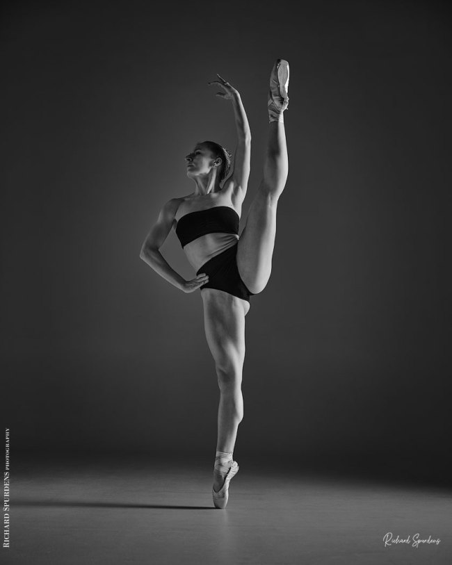 Dance Photographer - Dance photography - monochrome image of dancer standing on single pointe with the other leg lifted vertically up