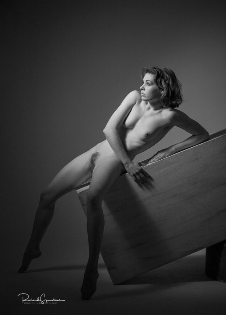 monochrome image showing a stong artistic nude figure shape using a plinth at an angle