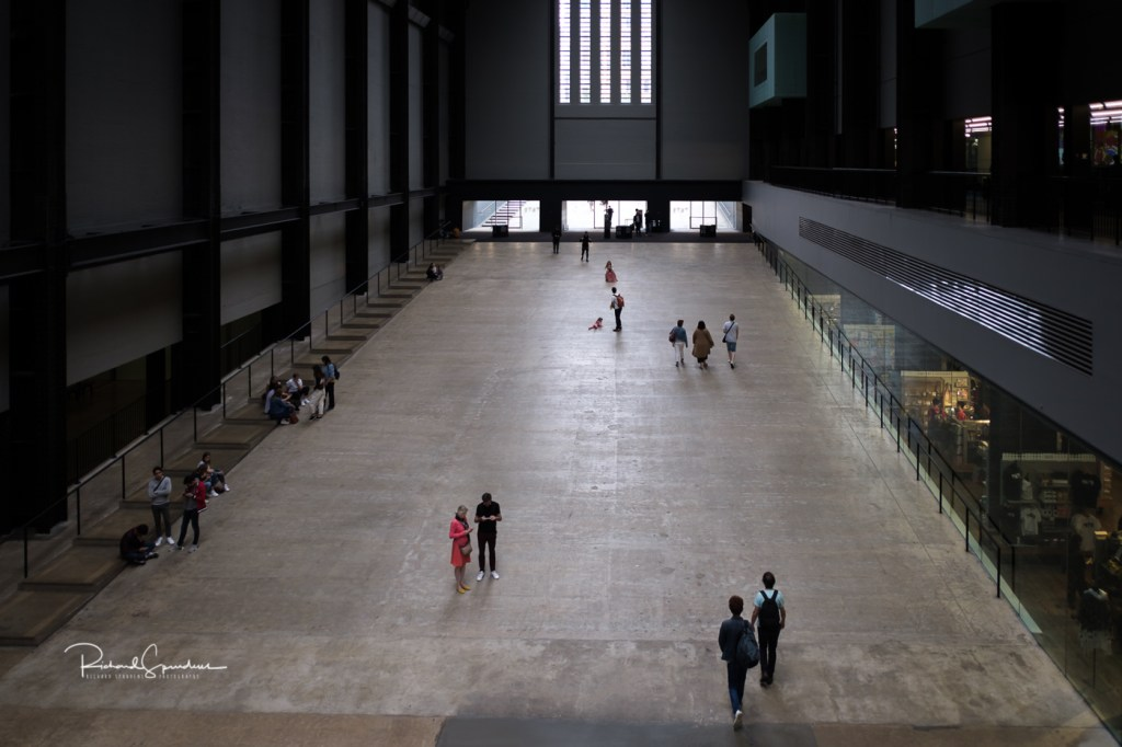 a shot looking down into the turbine hall at tate modern showing four small groups of people at various point on the vast floor