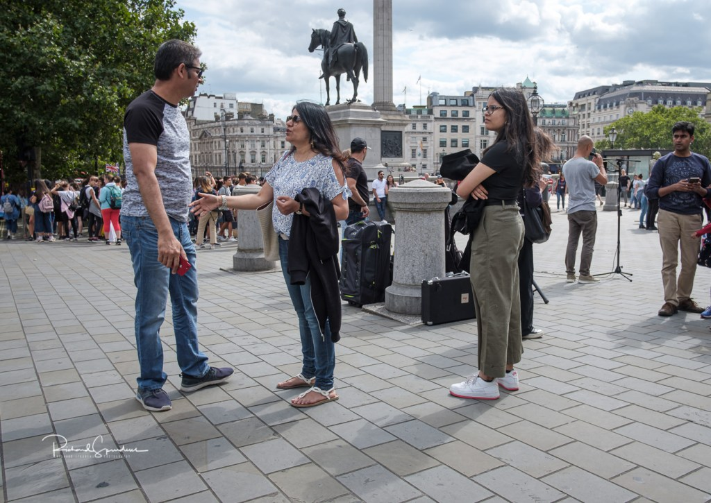colour image shot in trafalgar square of a family looking like they are in discussion about what to do next but each has a space between them so it look like a dispute. london views with my fuji xt-2