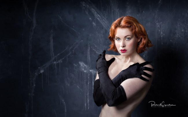 colour image featuring a red haired model wearing only black glove