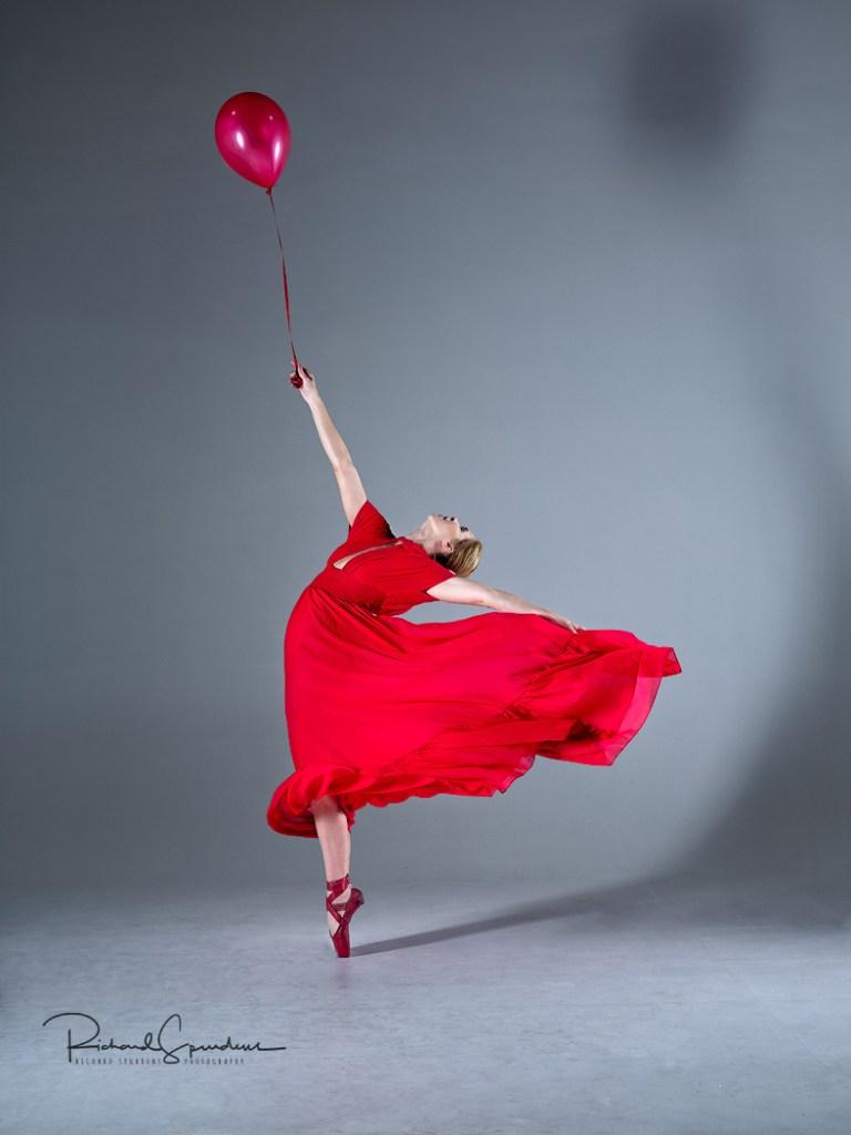 Image showing a dancer on pointe, wearing a red dress and holding a red balloon is it seems to pull her to the sky