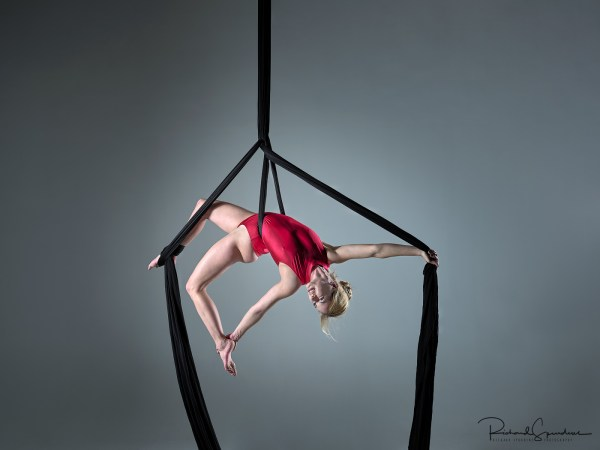 Colour image of aerialist fanny m hanging in a dynamic pose in mid air using aerial silks