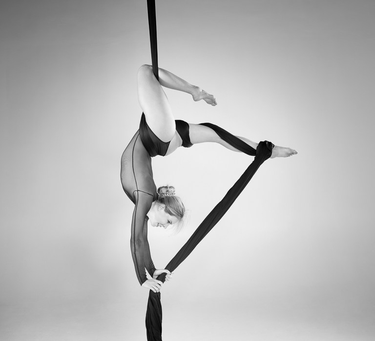 may print of the month - is a monochrome image of aerialist fanny muller using the silks to hang upside down stronge figure shapes using the body and silks