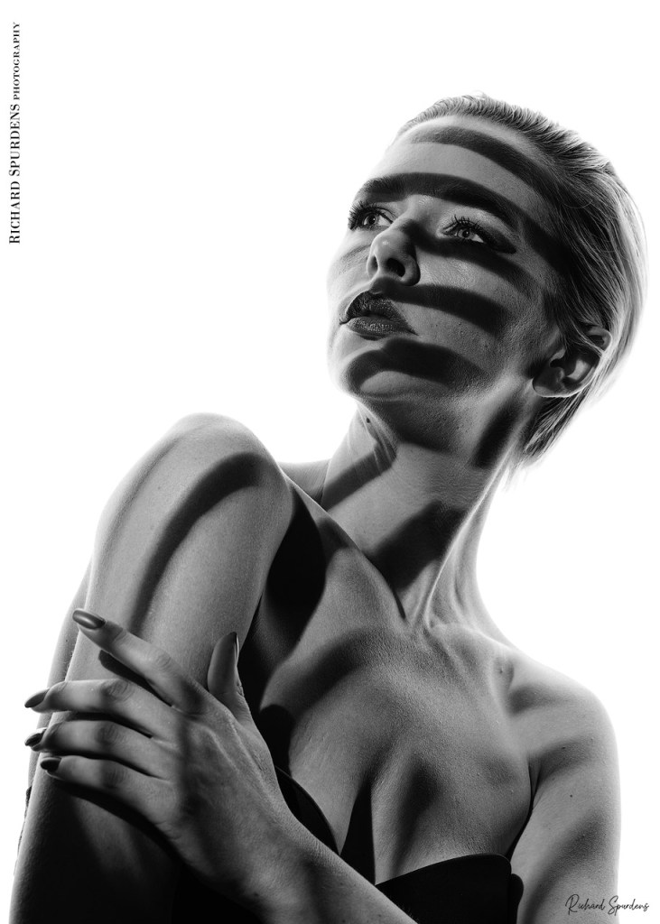 monochrome image from a virtual shoot with amie boulton using gobo shape projected on to the skin