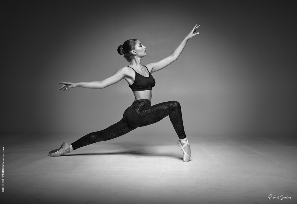 Dance Photographer - Dance Photography - monochrome image of dancer her front leg bent and held on poinet and her back leg out straight behinder her, she is look towards her right and arms are held a shoulder height forming a pleasing shape
