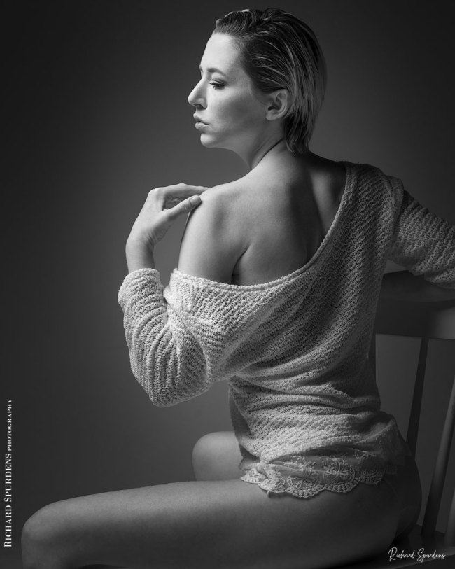 Fashion Photography - Fashion Photographer - monochrome image of model seated side on looking to her left into the light with her jumper off her shoulder left hand raise to her left shoulder