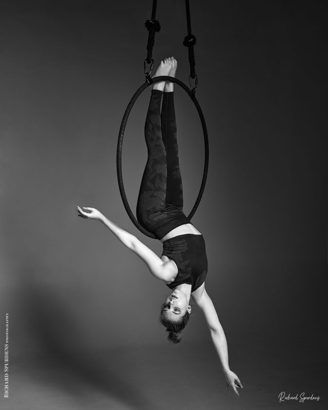 Aerial Arts photographer - Aerial hoop photographer - Aerial Arts photography - Aerial hoop photography -- monochrome image featuring aerialist ariel taylor hang vertically down from the aerial hoop holding on with her feet and arms held out to the side