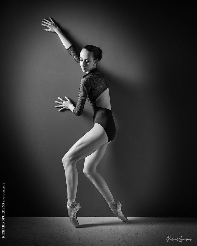 Dance Photographer - Dance photography - monochrome image of dancer making shapes against the wall lit from the side