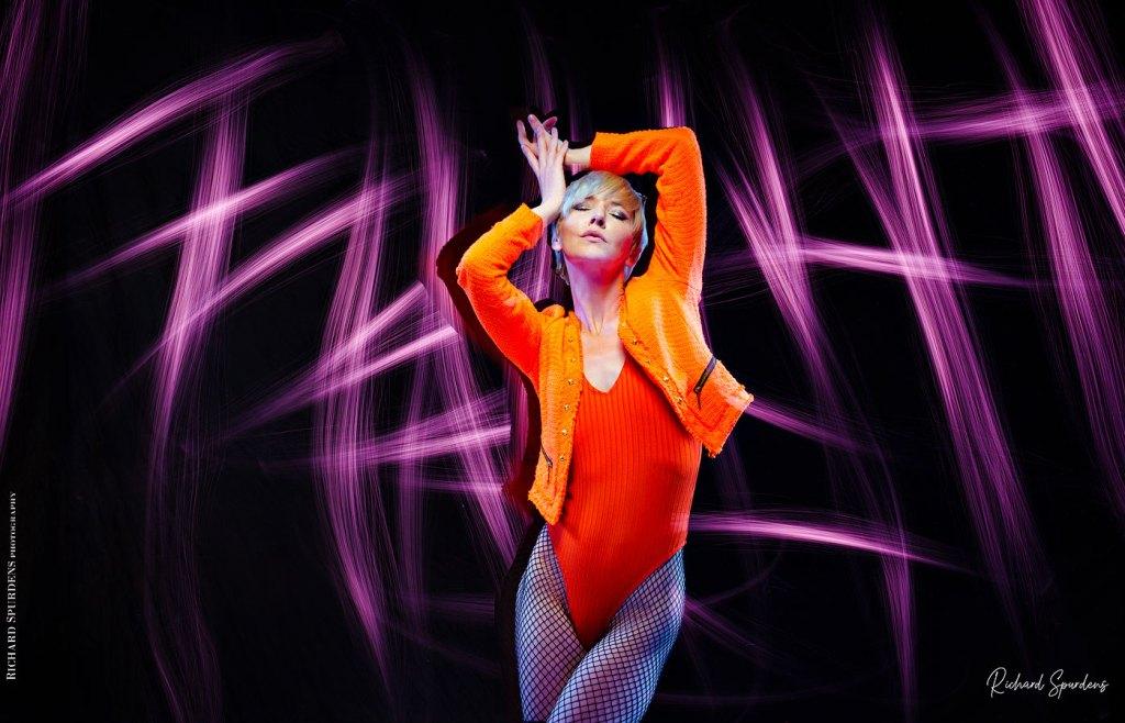 Fashion Photography - Fashion Photographer - colour image of model wearing orange jackets and body lighting swirls around the model using purple lights wands around the model