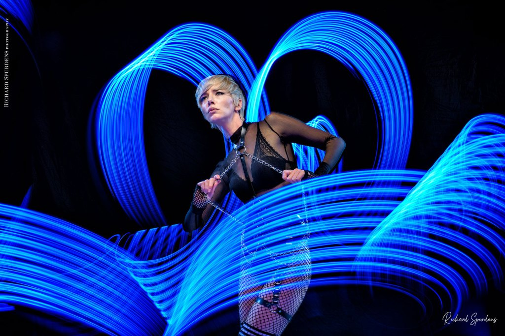 Light painting Photography - Fashion Photographer - colour image using a blue light painting wand creating blue swirls around the model