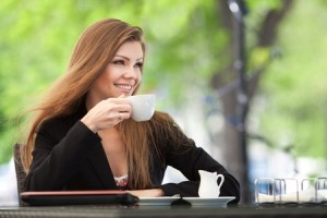 Brunette drinking coffee outdoor cafe