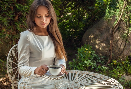 Brunette in white drinking coffee outdoors
