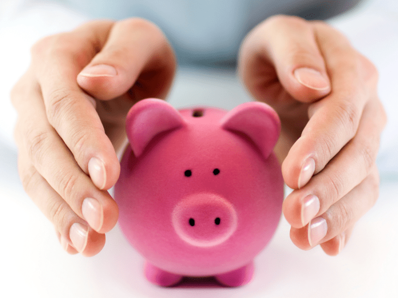 hands protecting money in a piggy bank from inflation