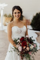 red, pink, and white large wedding bouquet with smiling bride
