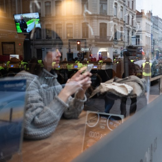 Woman in a bar using her phone during a demonstration