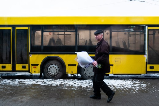 A man with flowers in front of a yellow bus