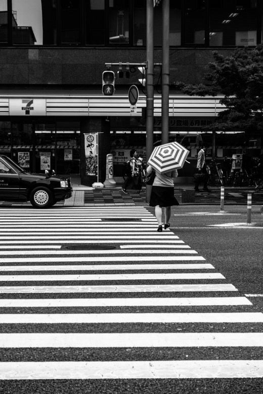 Crossroads, with a woman with a zebra umbrella under a 7eleven shop