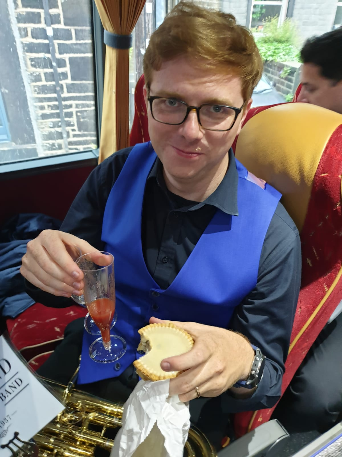 A player on the coach holding a champagne flute and a pork pie