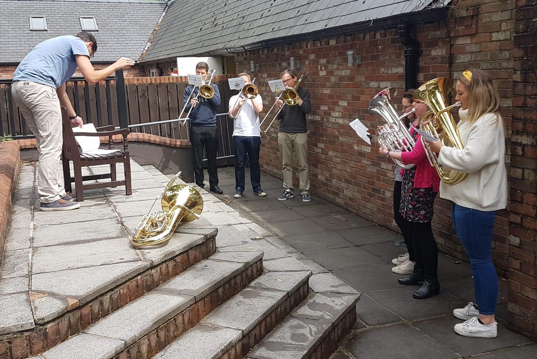 The trombones, euphoniums and baritones rehearse.