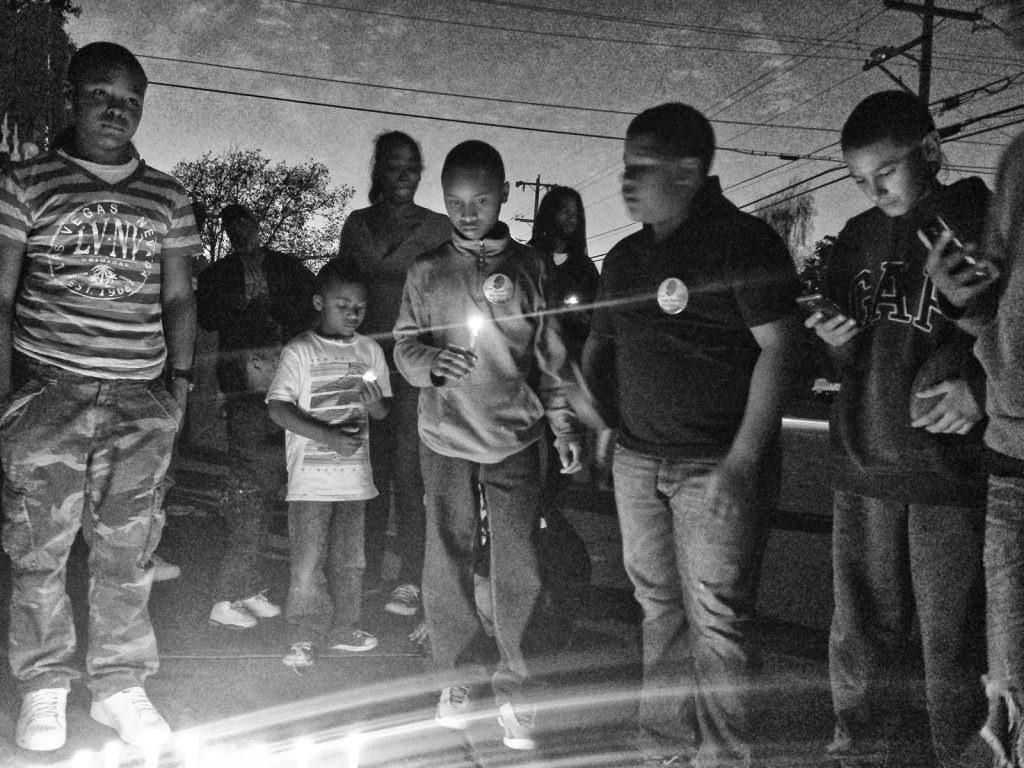 Friend's of Rodney Frazier, 16-year-old, light candles near the spot where he was killed outside of his home in North Richmond Saturday night. (Photo by Shawn Baldwin)