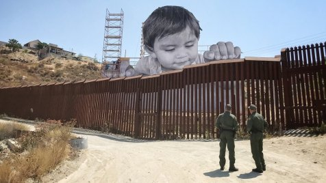 kid looking over the mexico-u.s. border wall