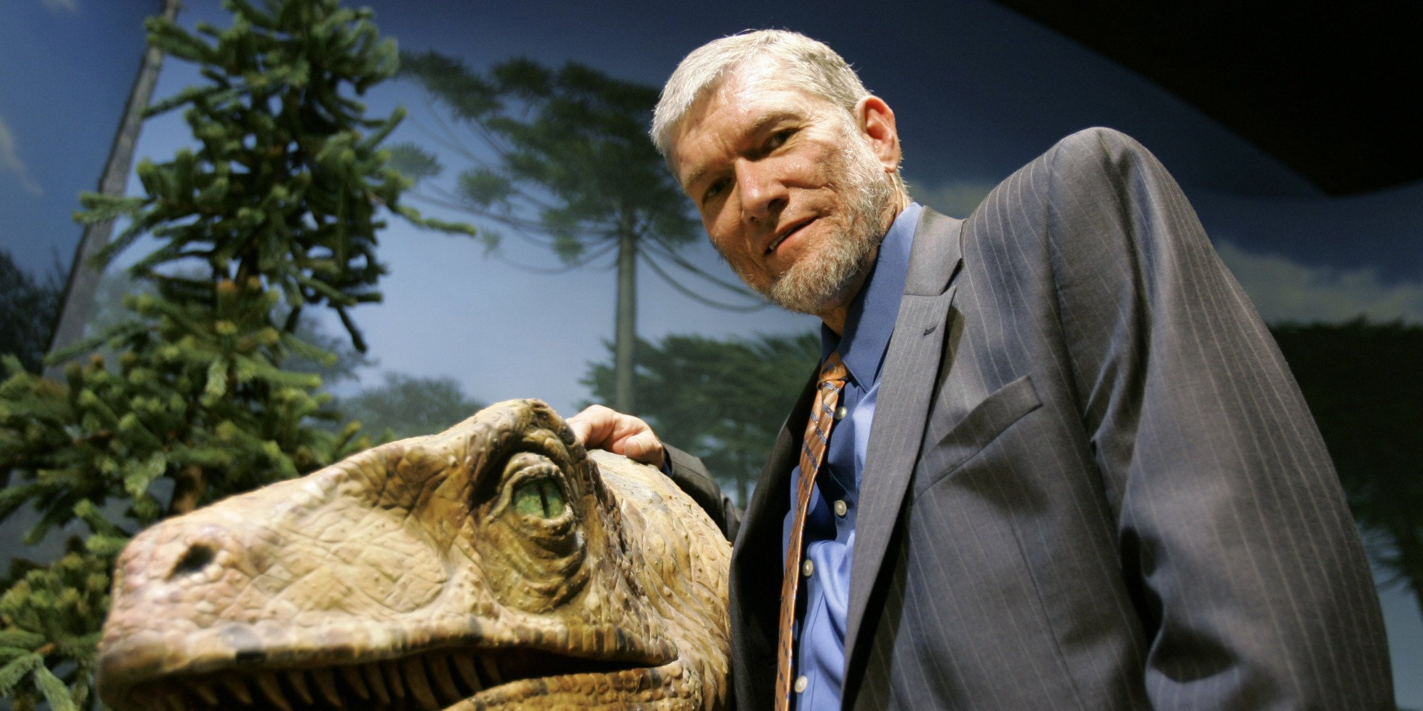 Ken Ham posing next to a dinosaur exhibit