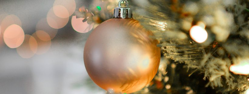 an amber-colored ornament ball hanging from a Christmas tree