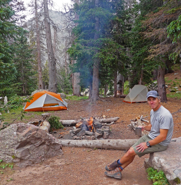 Text Box: My camping partner, Rick Peckham, is relaxed. Tents are up, clearing is flat, logs and big rocks to sit on, fire is going, protected by a makeshift rocky ring; mountains in the background – what could be better?