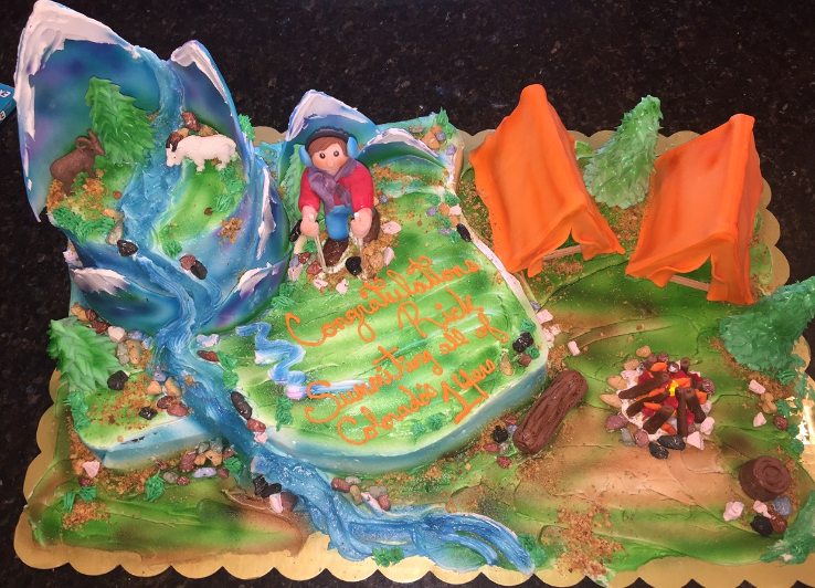 "A cake decorated with a mountain and camper, icing letters say ""Congrautlations Rick Summiting all of Colorado's 14ers"""