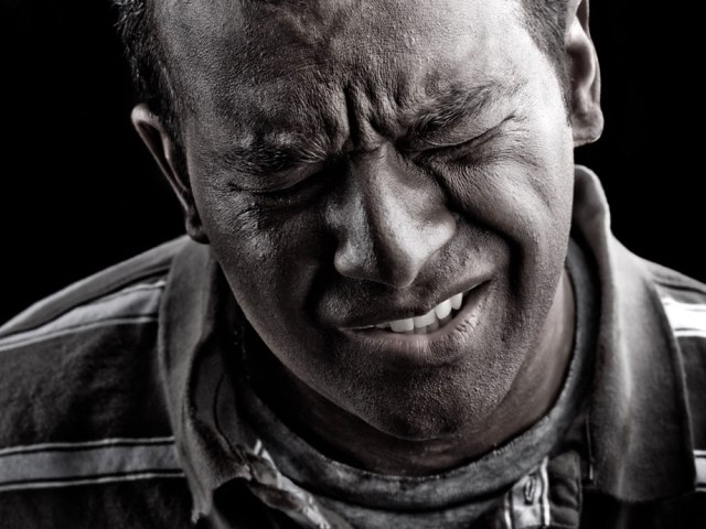 Black male with painful expression on his face