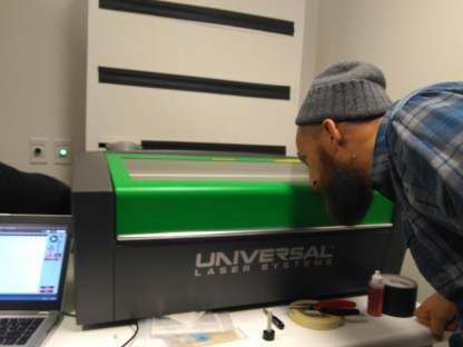 Andrew Rippeon (Visiting Assistant Professor of Literature) peers into the laser cutter while it engraves a woodblock.