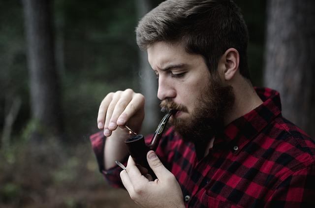 Un homme allumant sa pipe avec une allumette