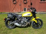 """The soon to be """"adventurized"""" Ducati Scrambler Icon. Note the dry bags and very small case guards that came with the bike."""