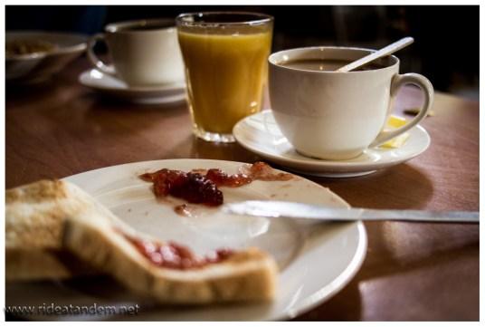 """Unsere schlechte Einkaufspolitik zwingt uns zum Frühstück im William Creek Hotel. Aber """"all you can eat"""" ist für hungrige Radler keine schlechte Lösung. Niko bringt es aus 12 Scheiben Toast, 2 Schalen Müsli, 6 Gläser Orangensaft, 2 Tassen Kaffee und ein bisschen Obst. Das reicht bis zum Mittag ;-)"""