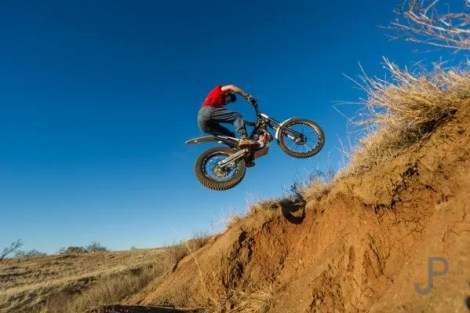 Chris Johnson jumps his trials motorcycle over a gap in the dirt at his ranch west of Lawton.